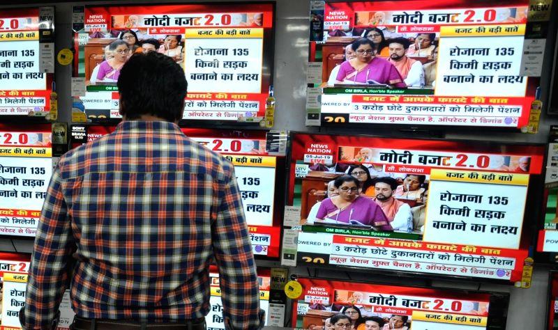 Kolkata: People busy watching the telecast of the presentation of Union Budget 2019 by Union Finance Minister Nirmala Sitharaman in the Lok Sabha; at an electronics showroom in Kolkata on July 5, 2019. (Photo: Kuntal Chakrabarty/IANS)