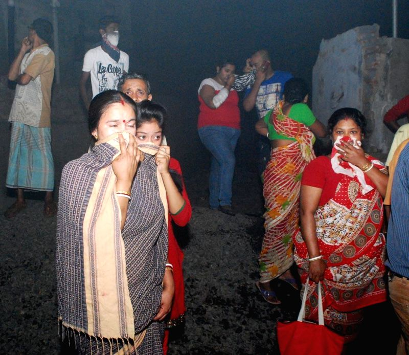 People cover their noses so as to avoid inhaling poisonous gases as a fire breaks out at a plastic godown in Kasba of Kolkata on March 1, 2015.