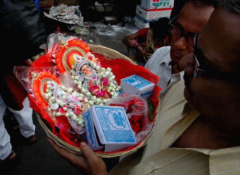 People hold the idols of lord Ganesha and Lakshmi for worship at a temple on `Poila Baisakh` - Bengali New Year, 1422 - in Kolkata, on April 15, 2015.