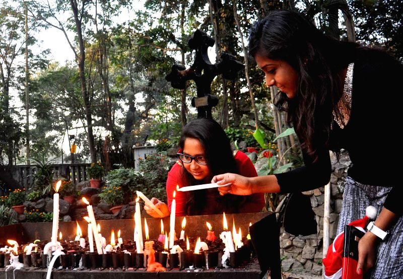 People light candles at St Paul's Cathedral on Christmas eve in Kolkata, on Dec 24, 2014.