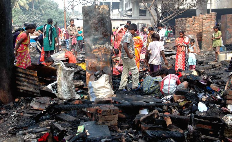 People look for their belongings in the remains of their houses destroyed in a fire that broke out in Duttabad, in Kolkata on Dec 4, 2014.