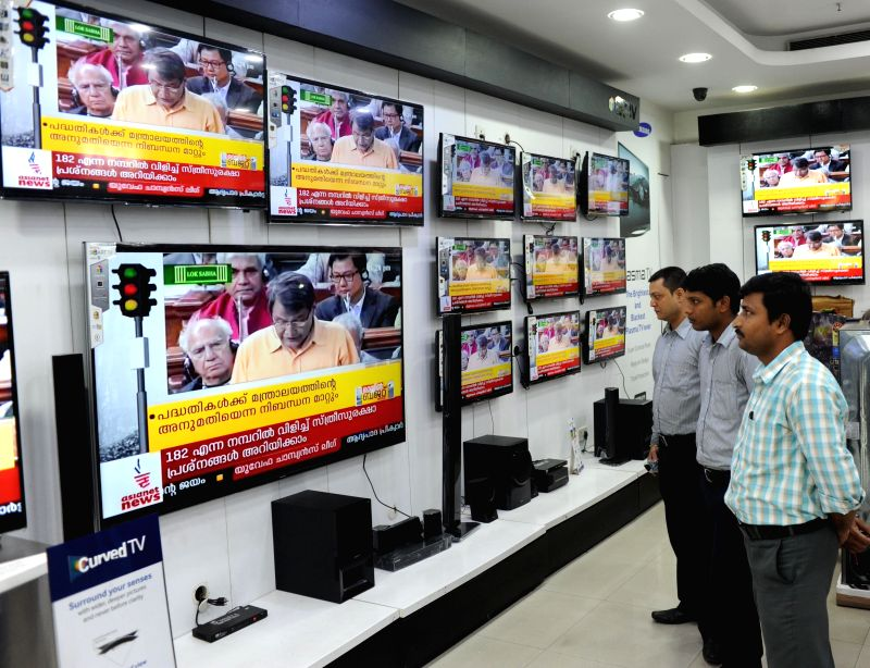 People watch Union Railways Minister Suresh Prabhakar Prabhu present Railway Budget 2015-16 on television sets in an electronic showroom in Kolkata, on Feb 26, 2015. - Suresh Prabhakar Prabhu