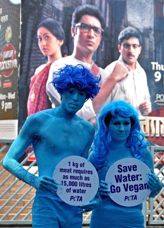 PETA activists raise slogans of `Save Water - Go Vegan` in Kolkata on March 20, 2015.