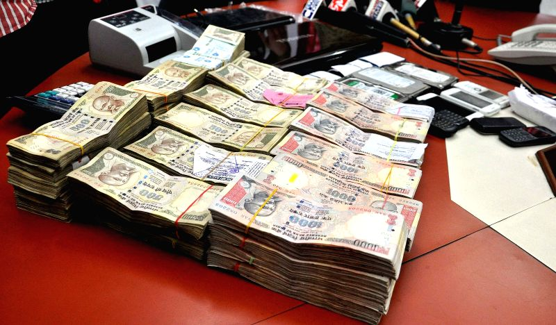 Policemen display the cash recovered by them after busting gang involved in Cricket World Cup betting in Kolkata, on March 25, 2015.
