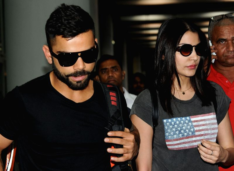 Royal Challengers Bangalore (RCB) captain Virat Kohli and actress Anuskha Sharma arrive at Netaji Subhas Chandra Bose Airport in Kolkata on April 6, 2015.