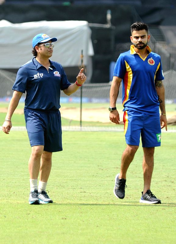 Royal Challengers Bangalore (RCB) captain Virat Kohli interacts with Mumbai Indians (MI) team icon Sachin Tendulkar during a practice session at the Eden Gardens in Kolkata, on April 7, ... - Virat Kohli and Sachin Tendulkar