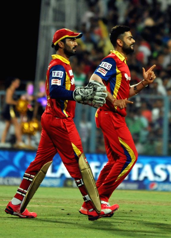 Royal Challengers Bangalore (RCB) captain Virat Kohli with teammate Dinesh Karthik celebrate fall of a wicket during an IPL-2015 match between Kolkata Knight Riders (KKR) and Royal ... - Virat Kohli