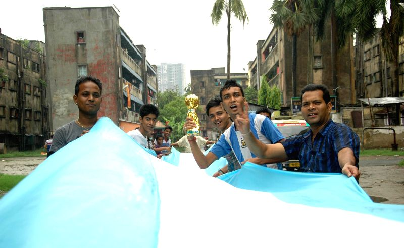 Kolkata`s football fans carry an Argentinian flag along a street in Kolkata on June 21, 2014.
