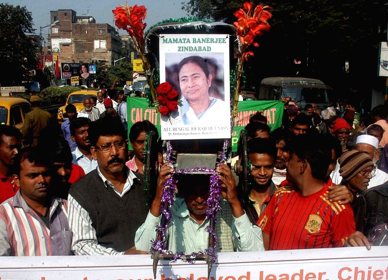 The members of All Bengal Rickshaw Union participate in a rally in favor of Mamata Banerjee led West Bengal Government in Kolkata on Dec 18, 2014.