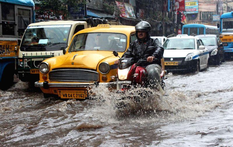 Kolkata: Vehicles wade through a water-logged road during rains triggered by severe cyclonic storm 'Bulbul', in Kolkata on Nov 9, 2019. (Photo: Kuntal Chakrabarty/IANS)