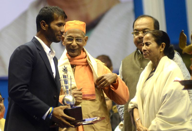 West Bengal Chief Minister Mamata Banerjee during Vivek Chetna Utsav ahead of 152 Birth anniversary of Swami Vivekananda in Kolkata, on Jan 10, 2015. Also seen cricketer Ashok Dinda and ...