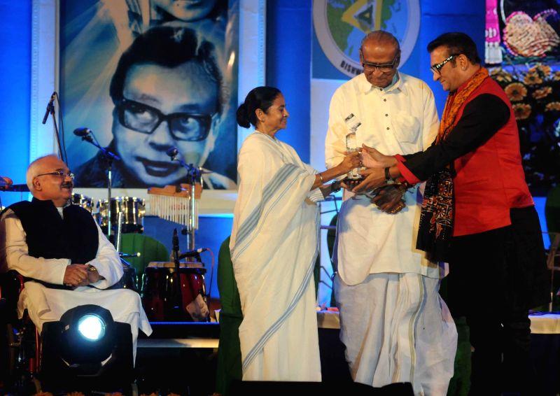 West Bengal Chief Minister Mamata Banerjee hands over the `Sangeet Mahasamman` to singer Abhijeet during `Bangla Sangeetmela` in Kolkata, on Feb 13, 2015. Also seen singers Dwijen Mukherjee . - Mamata Banerjee, Dwijen Mukherjee and Mohan Singh
