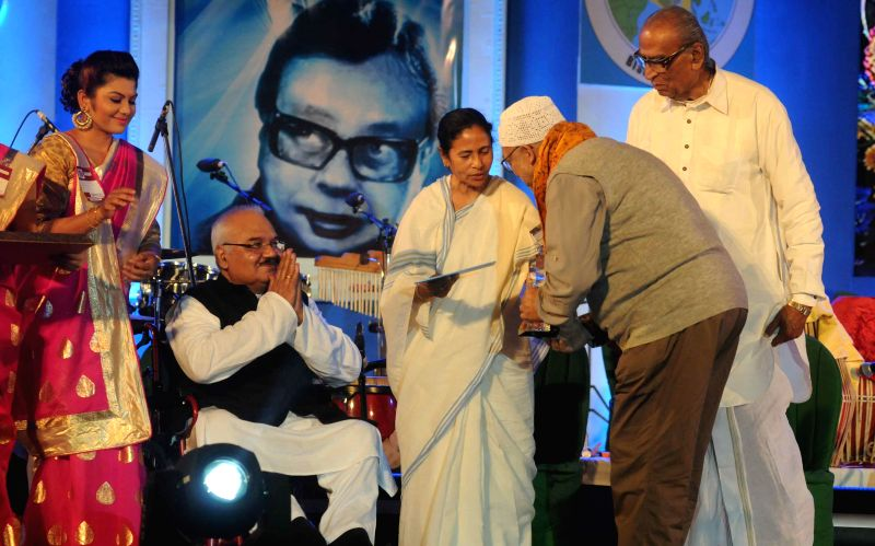 West Bengal Chief Minister Mamata Banerjee hands over the `Sangeet Mahasamman` to singer and former Trinamool MP Kabir Suman during `Bangla Sangeetmela` in Kolkata, on Feb 13, 2015. Also ... - Mamata Banerjee, Dwijen Mukherjee and Mohan Singh