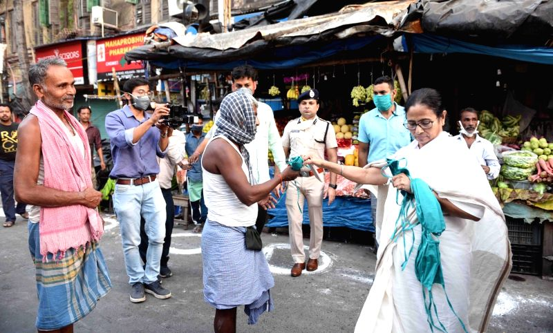 Kolkata: West Bengal Chief Minister Mamata Banerjee distributes masks among people on Day 2 of the 21-day nationwide lockdown imposed by the Narendra Modi government over the coronavirus pandemic; in Kolkata on March 26, 2020. (Photo: IANS)