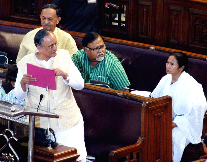 West Bengal Finance Minister Amit Mitra presents the state budget for 2015-16 at the state legislative assembly in Kolkata, on Feb 27, 2015. Also seen West Bengal Education Minister Partha ... - Amit Mitra, Partha Chatterjee and Mamata Banerjee