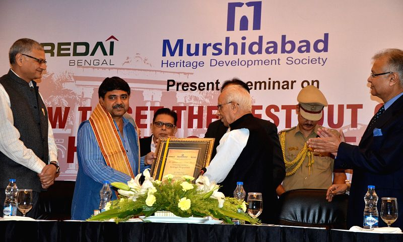 West Bengal Governor Keshari Nath Tripathi handover alife time achievement award to Director, Centre for Heritage Properties Debasish Nayak (L) at the inaugural session of the seminar and ...