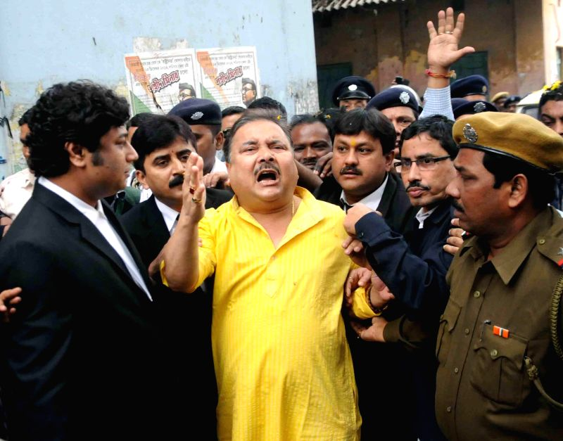 :Kolkata: West Bengal Transport Minister Madan Mitra being taken to be produced at a Kolkata Court in connection with the multi-crore-rupee Saradha chit fund scam in Kolkata, on Jan 16, 2015. ... - Madan Mitra