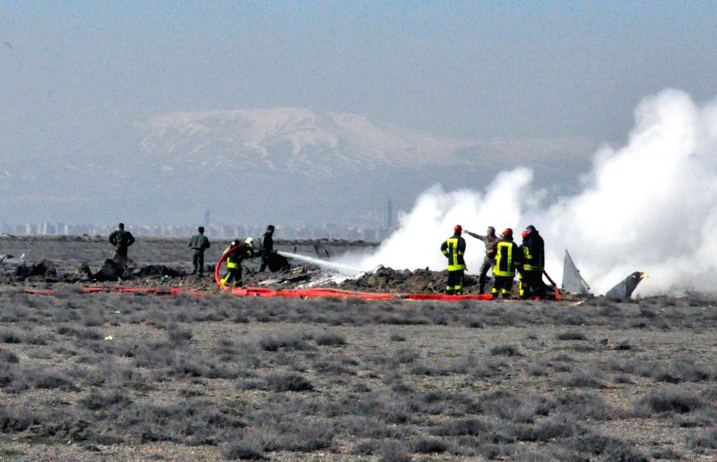 Emergency rescue team members work at the crash site in Konya province, Turkey, March 5, 2015. Two pilots were killed on Thursday when a military plane crashed in ...