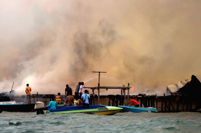 Residents try to put out the fire at the sea view villas at an island in Kota Kinabalu, the capital of Malaysia's state of Sabah, July 3, 2014. Some 50 cabins .