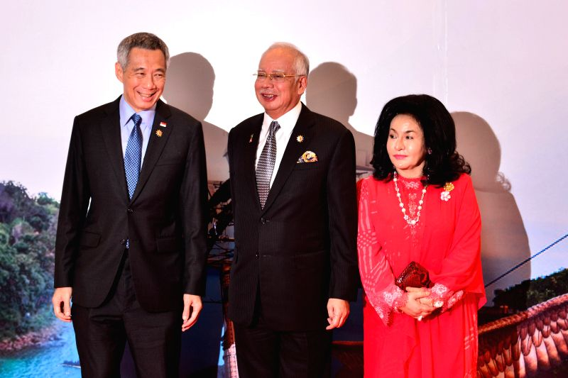 Malaysian Prime Minister Najib Razak (C) and his wife (R) meet with Singapore's Prime Minister Lee Hsien Loong before the opening ceremony of the 26th ... - Najib Razak