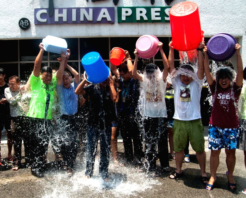 Staff members of the China Press participate in the ice bucket challenge in Kuala Lumpur, Malaysia, on Aug. 21, 2014.  The ALS Ice Bucket challenge, which ...