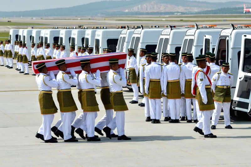 Malaysian Army soldiers carry a coffin during a repatriation ceremony at Kuala Lumpur International Airport in Sepang, Malaysia, Friday, Aug. 22, 2014. The ...