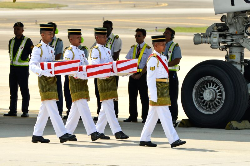 Malaysian Army soldiers carry boxs containing remains to hearses during a repatriation ceremony at Kuala Lumpur International Airport in Sepang, Malaysia, ...