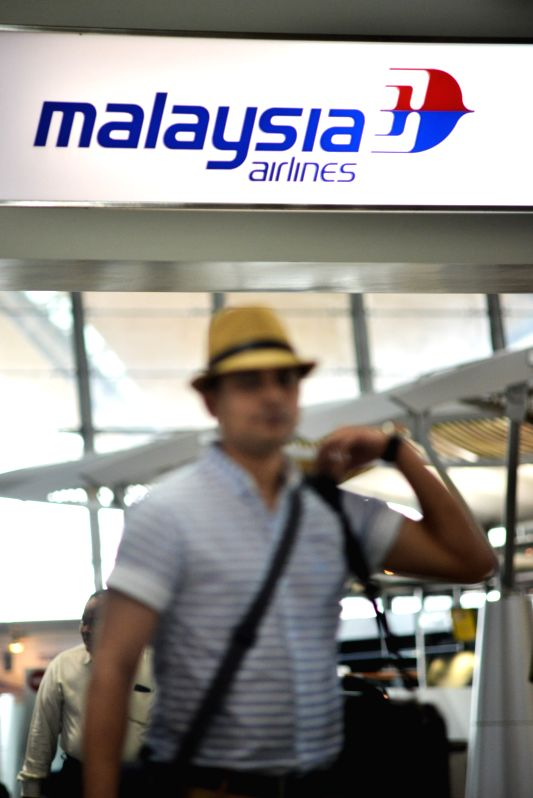 A passenger walks past the Malaysia Airlines counter at the Kuala Lumpur International Airport in Kuala Lumpur, Malaysia, Aug. 8, 2014. Khazanah Nasional Bhd, ..