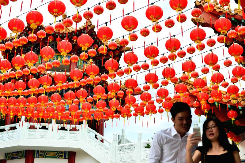 Tourists take pictures under red lanterns for the upcoming Chinese Spring festival in Kuala Lumpur, Malaysia, Feb. 4, 2015.