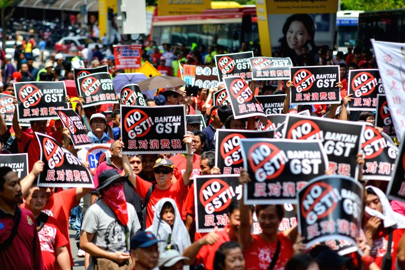 People gather during a protest against the Goods and Service Tax (GST), which is to be implemented in 2015, in Kuala Lumpur, Malaysia, on May 1, 2014. ...