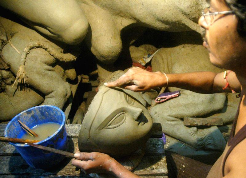 Kumartuli artists busy making idols of goddess Durga at a workshop in Kolkata on Aug 7, 2014.