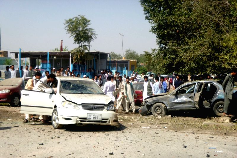 Afghans gather around destroyed vehicles after a blast in Kunduz Province, north Afghanistan, July 12, 2014. Earlier on Saturday, Local police commander Niyaz Khan .. - Niyaz Khan