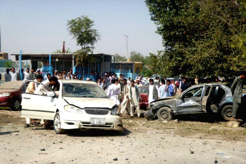 Afghans gather around destroyed vehicles after a blast in Kunduz Province, north Afghanistan, July 12, 2014. Earlier on Saturday, Local police commander Niyaz Khan .. - Niyaz Khan