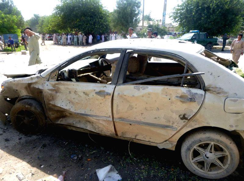 Afghans gather around a destroyed vehicle after a blast in Kunduz Province, north Afghanistan, July 12, 2014. Earlier on Saturday, Local police commander Niyaz Khan . - Niyaz Khan