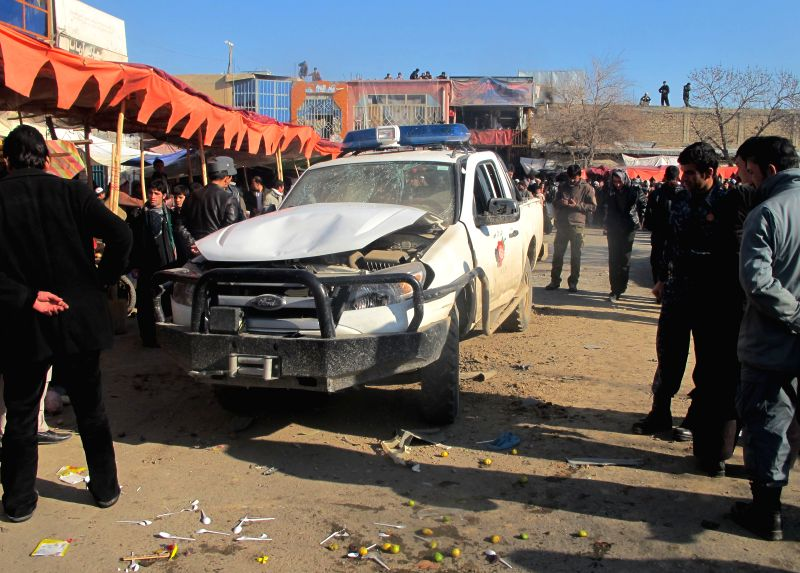 Members of Afghan security forces gather around a damaged police vehicle following a blast in Kunduz province in northern Afghanistan, Dec. 16, 2014. Casualties are still unknown. ...