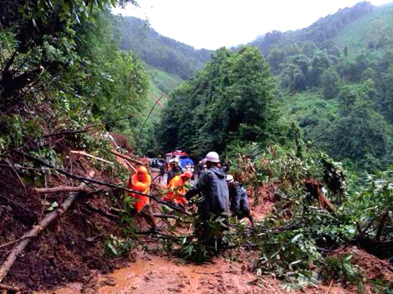 Photo taken with a mobile phone shows rescuers clearing the debris after a mudslide hit Lyuying Village in Dai-Jingpo Autonomous Prefecture of Dehong, southwest ...