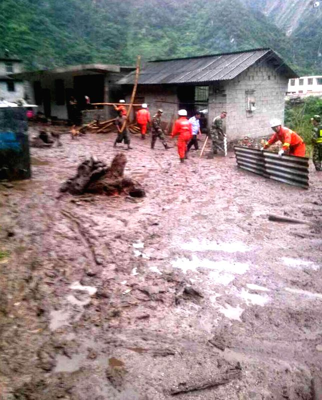 Photo taken with a mobile phone shows rescuers clearing the debris after a mudslide hit Shawa Village in Fugong County, southwest China's Yunnan Province, July 9, ...