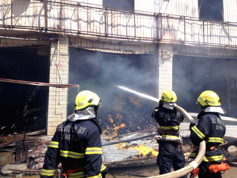 Firefighters work in this picture taken with a cellphone at the Dongmeng Lianfeng Agricultral Trade Center in the Guandu District of Kunming, capital of southwest ...