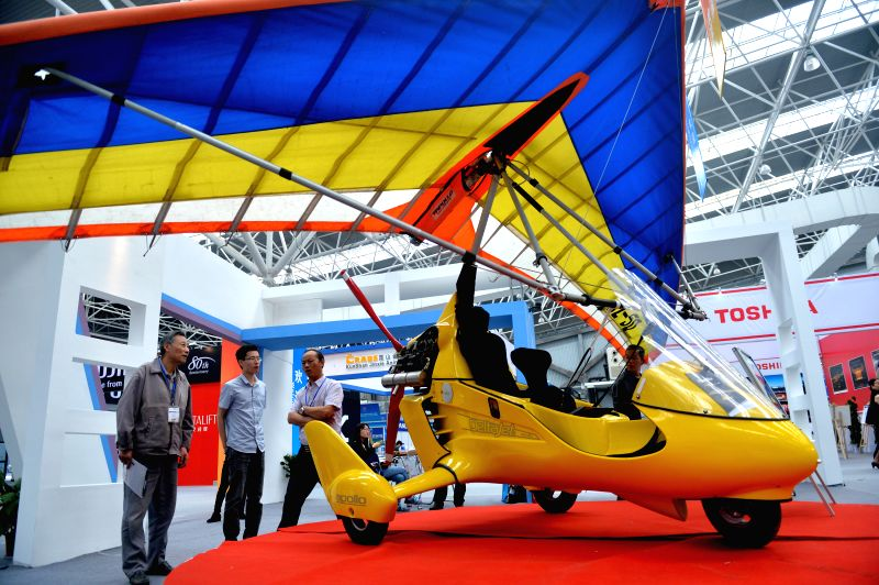 People visit a delta-wing aircraft during the 2014 China (Kunshan) Import Expo in Kunshan, east China's Jiangsu Province, May 14, 2014. The 4-day expo kicked off ...