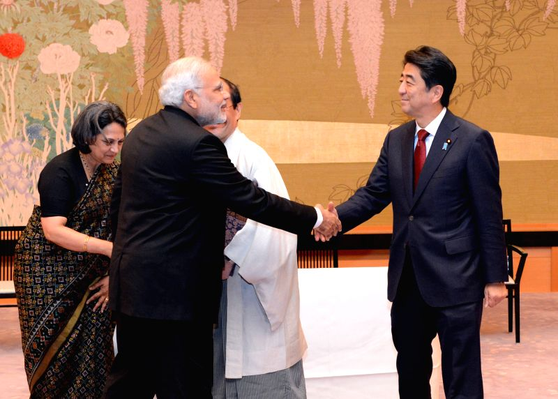Indian Prime Minister Narendra Modi (front L) shakes hands with Japanese Prime Minister Shinzo Abe during a signing ceremony to establish sister city ties between ... - Narendra Modi