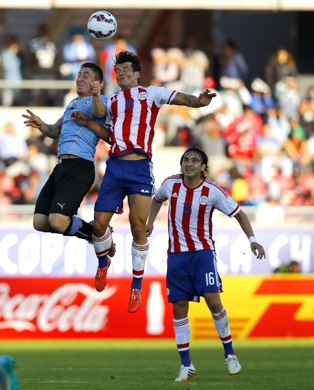 La Serena: Uruguayan midfielder Cristian Rodriguez (L) fights for the ball with Paraguayan striker Nelson Haedo Valdez (C) during the Copa America 2015 Group B soccer match between Uruguay and ...
