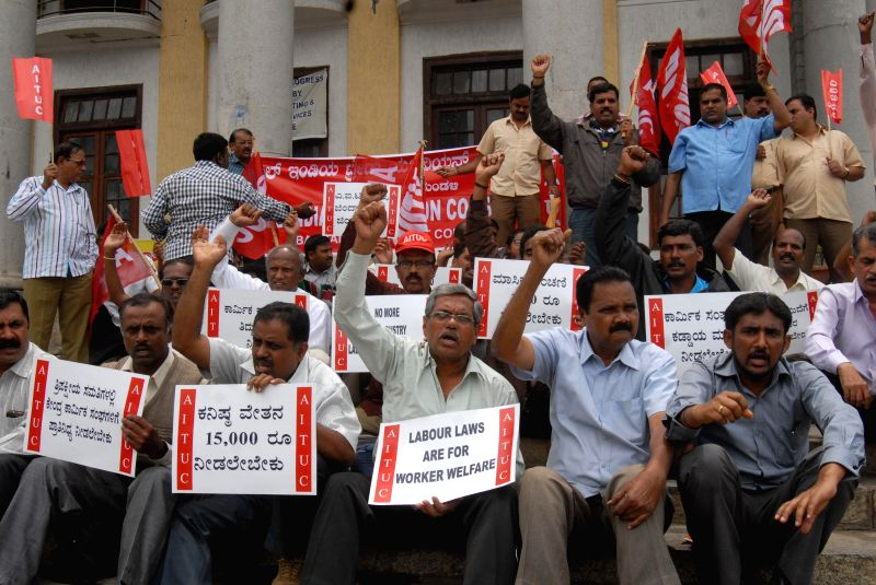 Labourers affiliated to AITUC stage a demonstration to press for a hike in their salaries at Freedom Park in Bangalore on Aug 18, 2014.