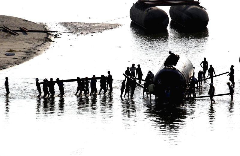 Labourers busy building a pontoon bridge over the Ganga river ahead of 'Magh Mela' festival in Allahabad on Nov 30, 2017.