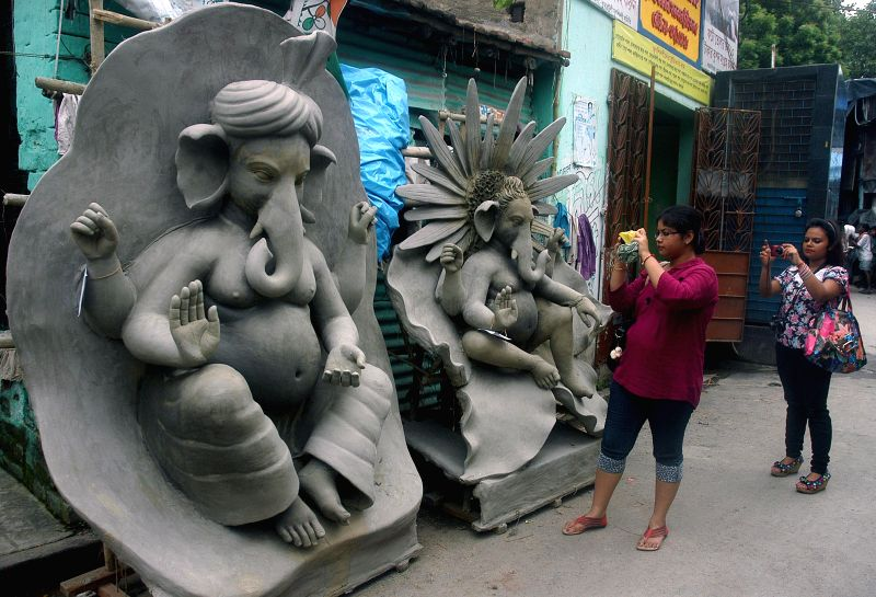 Ladies capture Ganesh idols in their lenses  at a Kumartuli workshop ahead of Ganesh Chaturthi in Kolkata on Aug 25, 2014.