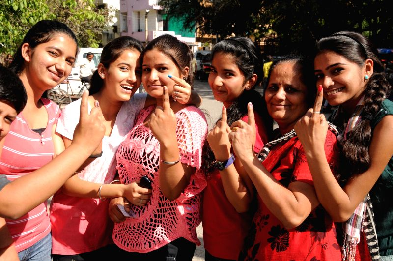 Ladies show their fore fingers marked with phosphorous ink after casting their votes at a polling booth during the third phase of 2014 Lok Sabha Polls in New Delhi on April 10, 2014. Elections are ...