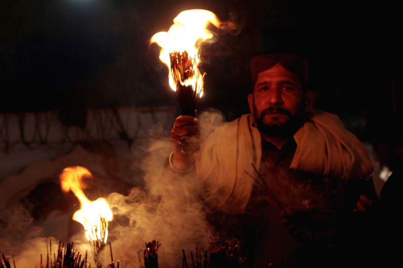"""A Pakistani Muslim devotee holds candles at the shrine of Hazrat Ali Bin Usman, popularly known as Data Gunj Bakhsh, during the annual """"Urs"""" religious festival in eastern Pakistan's"""