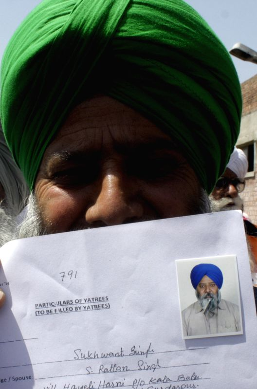 An Indian Sikh pilgrim shows his documents at Wagah Railway Station in eastern Pakistan's Lahore on April 10, 2014, to celebrate Baisakhi, or the Sikh New Year. ...