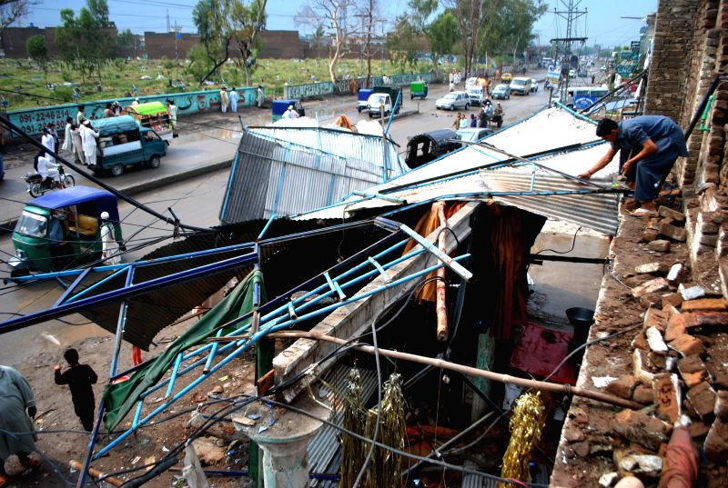 A man examines his damaged shop after heavy rain in northwest Pakistan's Peshawar on April 28, 2015. At least 30 people were killed and 150 others injured in ...