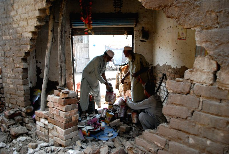 Residents examine their damaged home after heavy rain in northwest Pakistan's Peshawar, April 28, 2015. At least 30 people were killed and 150 others injured in ...
