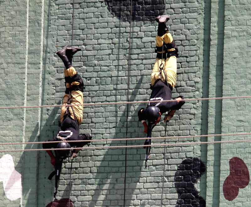 Police commandos display their skills during a passing out parade, upon the completion of their three-month training at Pakistan Ranger (Punjab) Headquarters in ...